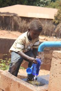 """FairWater BluePump Tappunt met Blue-Bottle in Gambia. FairWater partners vervangen met de BluePump de vele fragiele """"Plof-pompjes"""" die vaak nutteloos wegroesten. Met een eigen Blue-Bottle waterflesje heeft elk kind voortaan altijd water bij de hand. Dat is effectief en transparante hulp."""